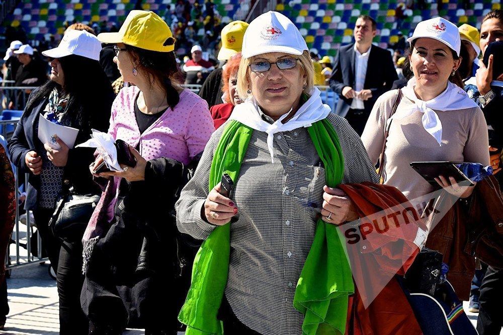 Женщина перед началом католической мессы Папы Римского Франциска на стадионе имени Михаила Месхи