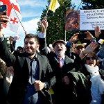Люди приветствуют кортеж Папы Римского Франциска на одной из улиц грузинской столицы