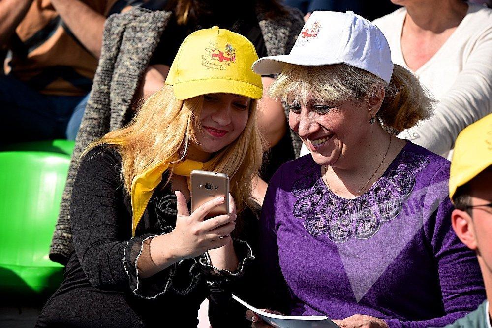 Верующие смотрят снятые на смартфон фотографии Папы Римского Франциска во время католической мессы на тбилисском стадионе имени Михаила Месхи