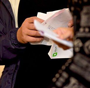 Выборы в Грузии - люди держат в руках бюллетени для голосования