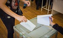 Женщина бросает концерт в избирательную урну на парламентских выборах в Грузии