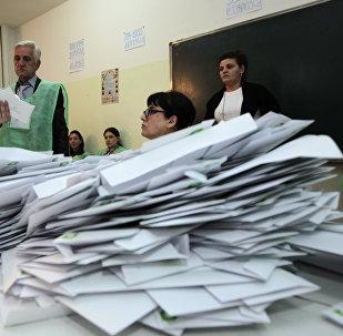 Члены избирательной администрации после выборов на одном из участков подсчитывают голоса