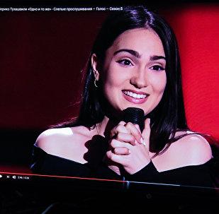 Девушка смотрит выступление Верико Тухашвили на проекте Голос