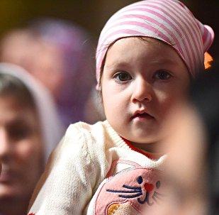Ребенок на руках у своей мамы во время службы в храме Светицховели во Мцхета