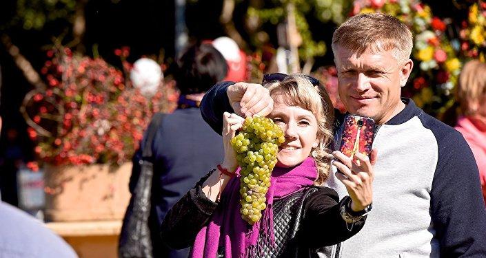 Туристы на празднике Тбилисоба делают селфи с виноградом