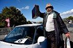 Турист из Индии на празднике Тбилисоба фотографируется на память во время посещения выставки ретро-автомобилей