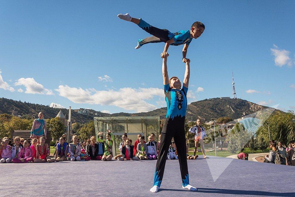 Солнечная и теплая погода в середине октября оказалась на руку юным гимнастам, которые в минувшие выходные демонстрировали свое мастерство на площади Рике в историческом центре Тбилиси.