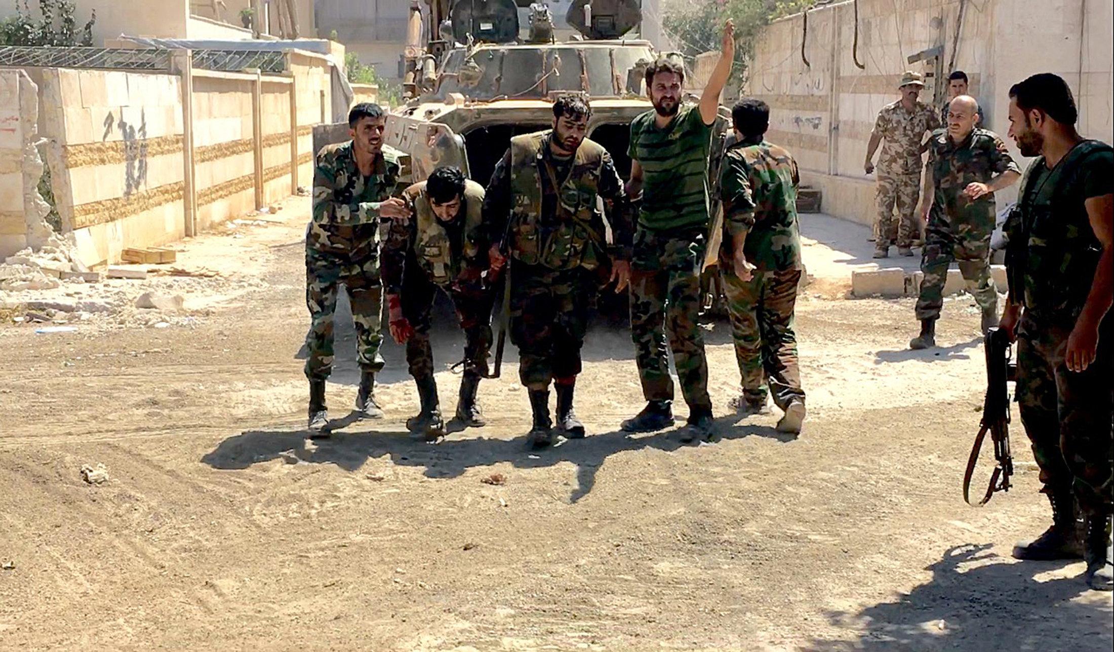 სირიის არმიის მებრძოლებს შეტევისას დაჭრილი თანამებრძოლი სამშვიდობოს გაჰყავთ