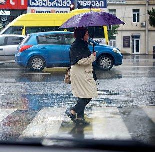 Женщина с зонтом переходит дорогу в дождь