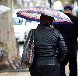 Похолодание в Тбилиси - люди идут по улице в дождь