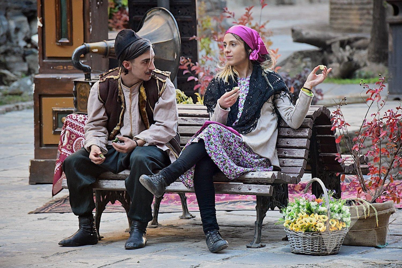 Молодые люди в старинной одежде беседуют на улице в историческом центре столицы Грузии