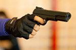 Человек держит в руках пистолет