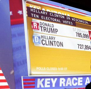 Человек наблюдает за показом данных в ходе подсчета голосов на выборах президента США