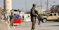 Служащий Национальной армии Афганистана у базы Баграм в Афганистане после взрыва
