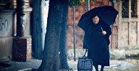 Женщина идет дождливым утром по грузинской столице