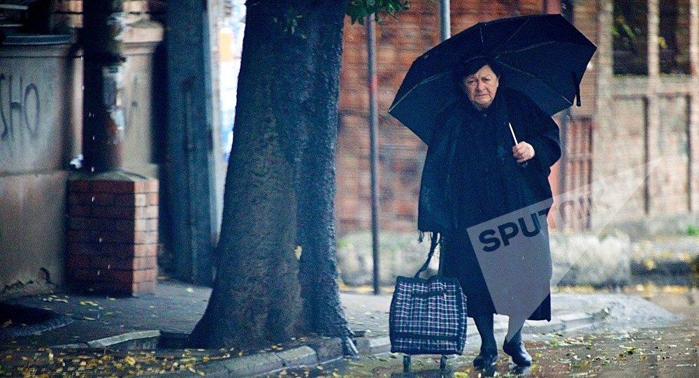 ქალი წვიმიან ამინდში თბილისის ქუჩაში