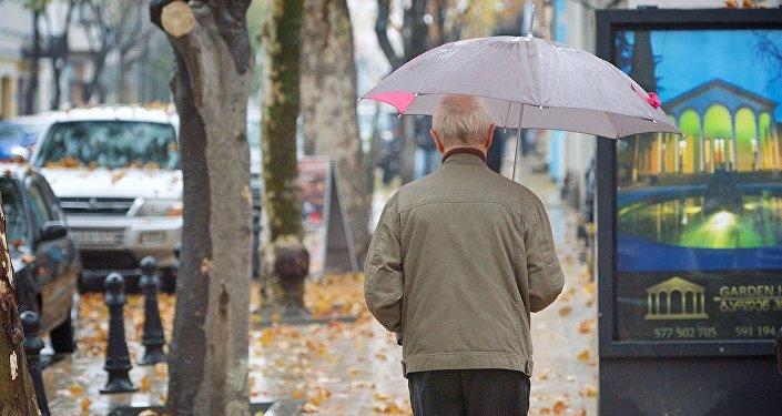 Прохожий идет дождливым утром по грузинской столице