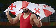 Борец Гено Петриашвили держит флаг Грузии, празднуя победу