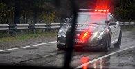 Полицейская машина едет по трассе в дождь