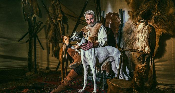 Мужчина с охотничьими собаками на фоне звериных шкур на фотографии Вано Пицхелаури