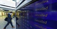 Пассажир проходит мимо табло с информацией об отмене рейсов во время забастовки пилотов немецкой авиакомпании Люфтганза в аэропорту Франкфурта