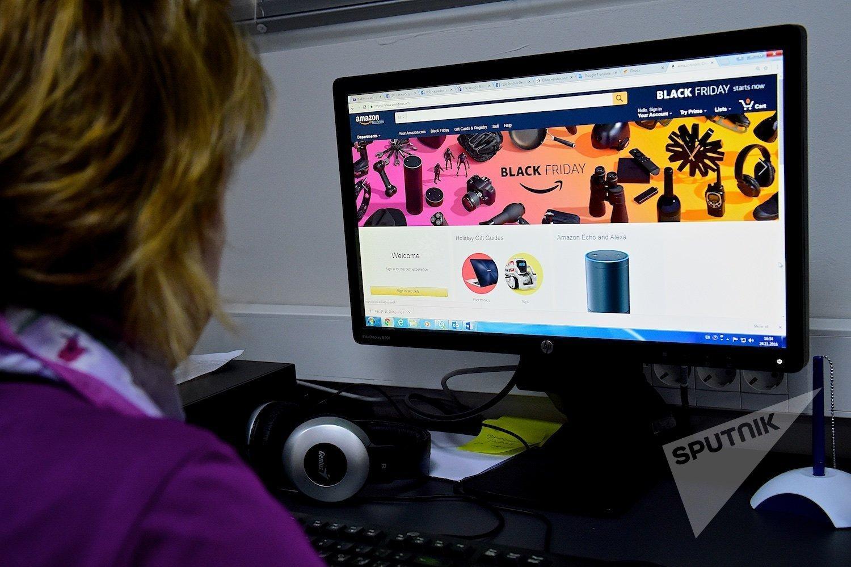 Девушка рассматривает объявление о Black Friday (Черная пятница) на экране компьютера