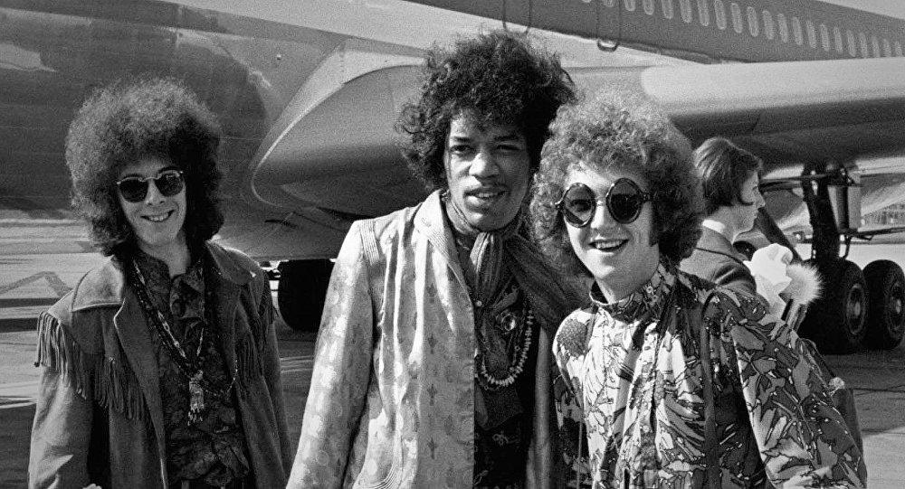 Джими Хендрикс (в центре), бас-гитарист Ноэл Реддинг (слева) и ударник Мич Митчелл (справа) на фото, сделанном в 1967 году в аэропорту Хитроу