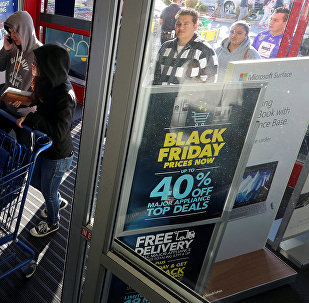 Покупатели входят в один из магазинов в США на фоне объявлений о Черной пятнице