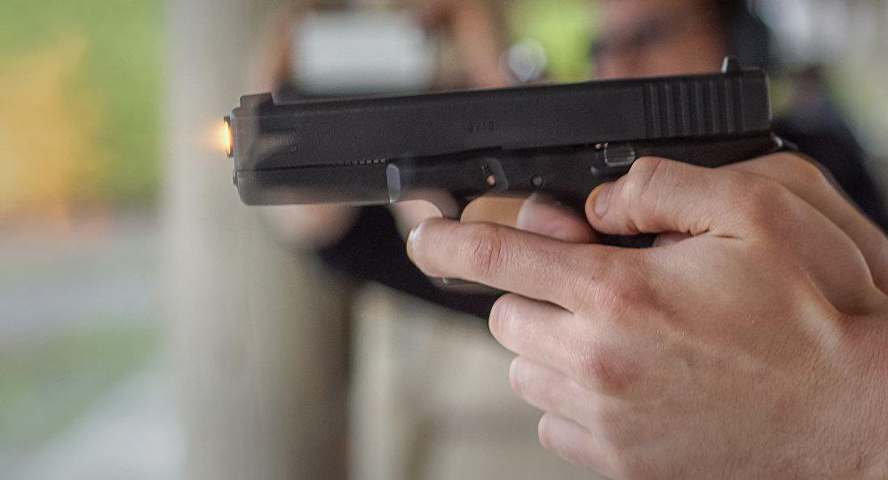 Мужчина стреляет из пистолета по мишени в стрелковом клубе