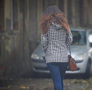 Девушка идет холодным осенним днем по одной из улиц столицы Грузии
