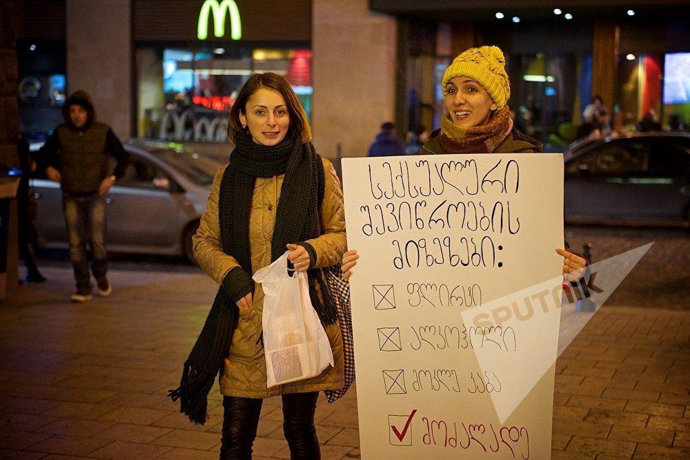Одна из девушек держит плакат Цели притеснения по сексуальному признаку. Как формы давления на женщин со стороны мужчин указаны запрет на флирт, на ношение коротких платьев и на употребление алкоголя. В то же время галочкой отмечен пункт Насилие разрешено.