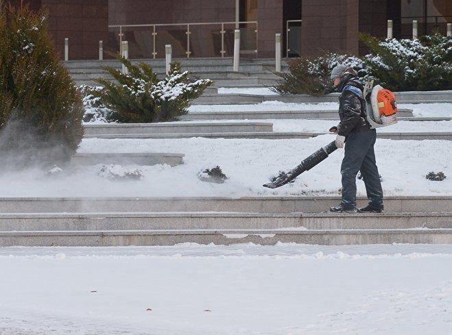 Сотрудники коммунальных служб очищают подъезды к месту встречи глав МИД от выпавшего Минске ночью снега