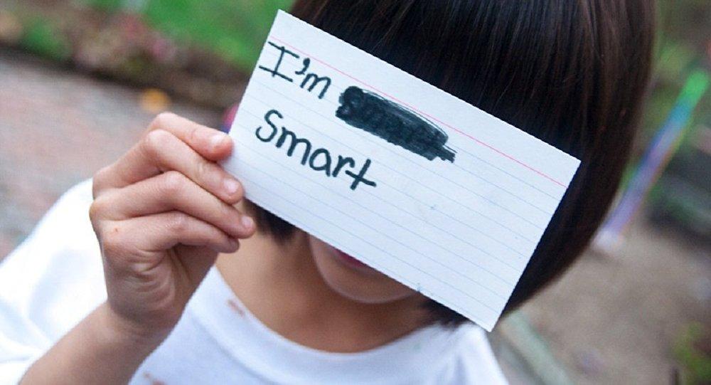 Девочка прикрывает глаза листочком с надписью Я умная