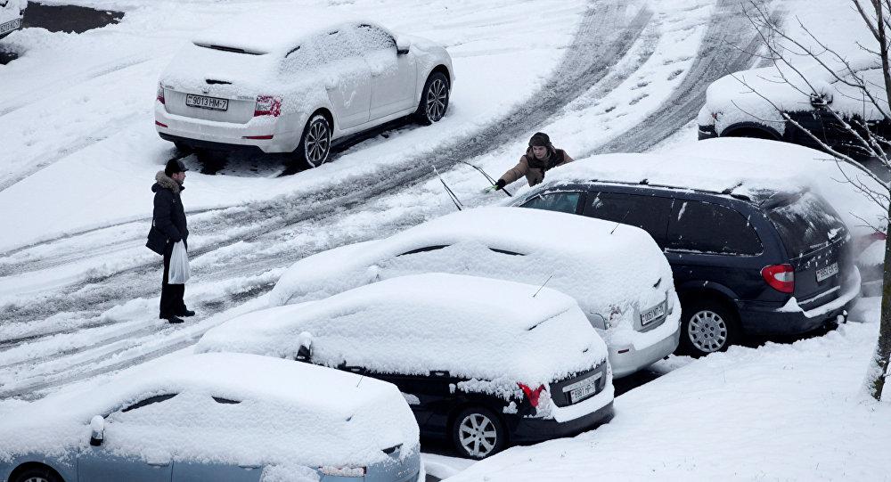 Мужчина очищает одну из припаркованных машин от снега
