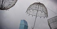 Металлический декоративный зонтик на фоне туч над городом