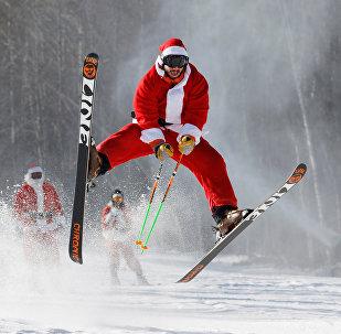Лыжник в костюме Санты участвует в благотворительном заезде Санта-Клаусов на американском горнолыжном курорте River Resort в штате Мэн