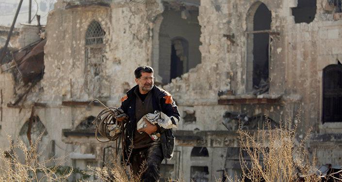 Мужчина, вернувшийся чтобы осмотреть свой дом, идет по контролируемой правительством территории в старом городе Алеппо, Сирия