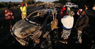 Люди смотрят на машину, пострадавшую в ДТП с автоцистерной в 80 километрах от столицы Кении Найроби