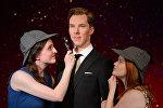 Фанатки Дейзи Ингланд (слева) и Чарли Митчел (справа) фотографируются в шляпах в стиле Шерлока Холмса и с увеличительным стеклом рядом с новой восковой фигурой британского актера Бенедикта Камбербэтча в музее Мадам Тюссо в Лондоне