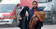 Мужчина несет ребенка с капельницейй в Алеппо, Сирия