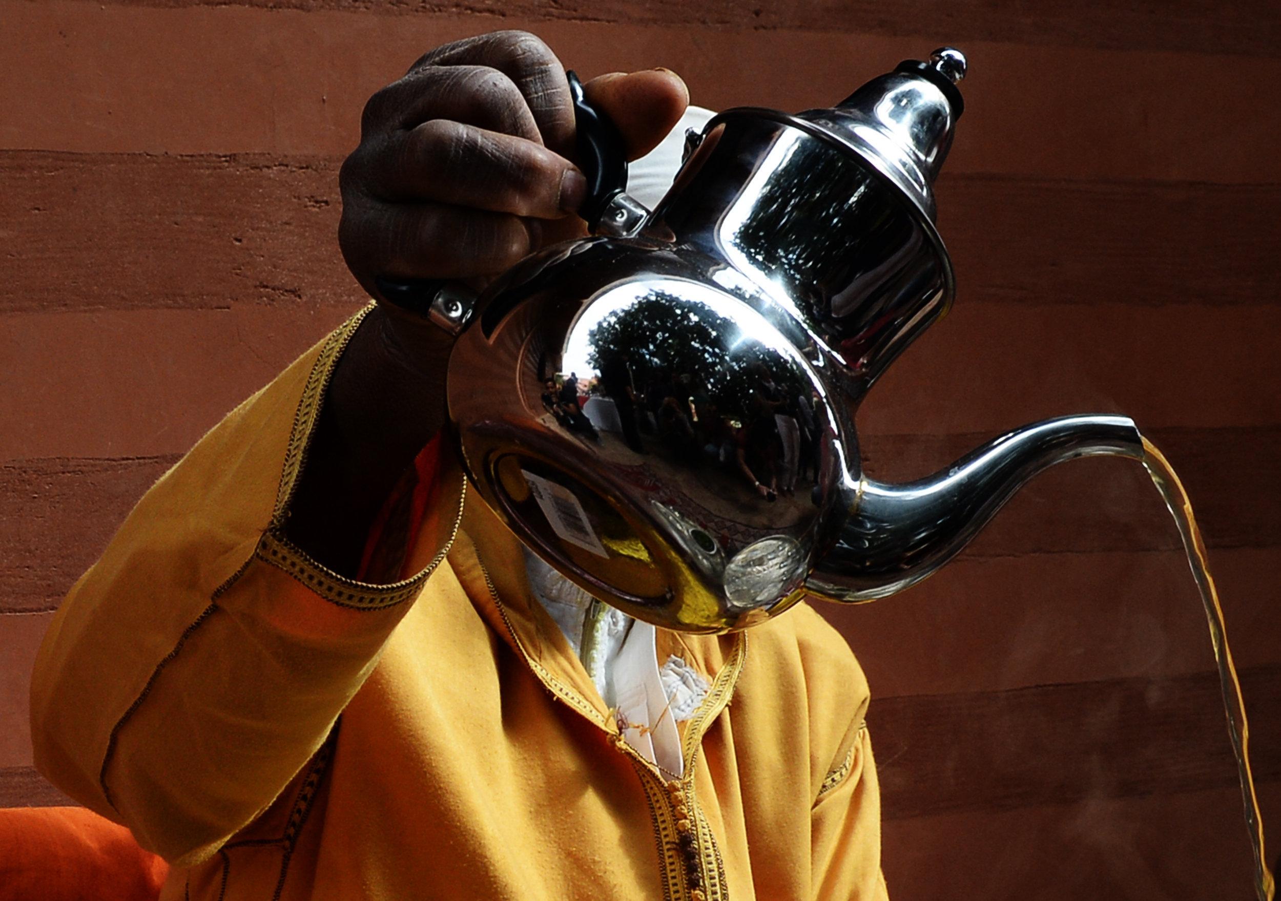 Мужчина готовит чай для туристов в Агадире