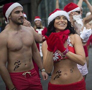 Группа людей, одетых в колпаки Санта Клауса и купальные костюмы, принимают участие в тринадцатом благотворительном забеге Санта Клаусов в Будапеште, Венгрия