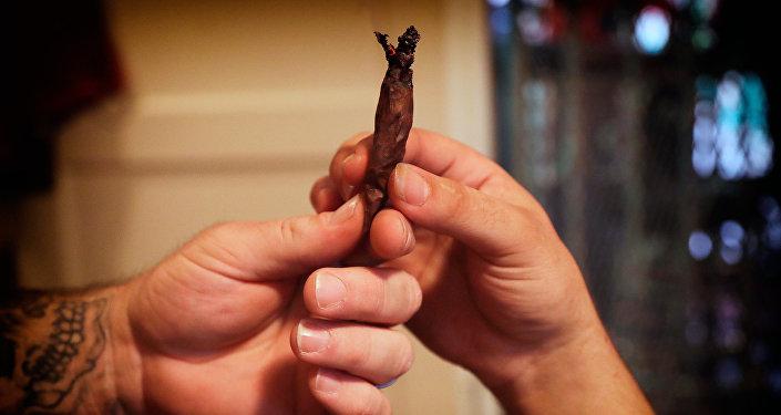 Два человека передают друг другу сигаретку из марихуаны