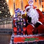 Ребенок фотографируется на память с Дед Морозом у главной новогодней елки Грузии на проспекте Руставели