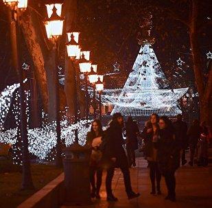 Новогодний Тбилиси - люди гуляют по проспекту Руставели, освещенному праздничной иллюминацией
