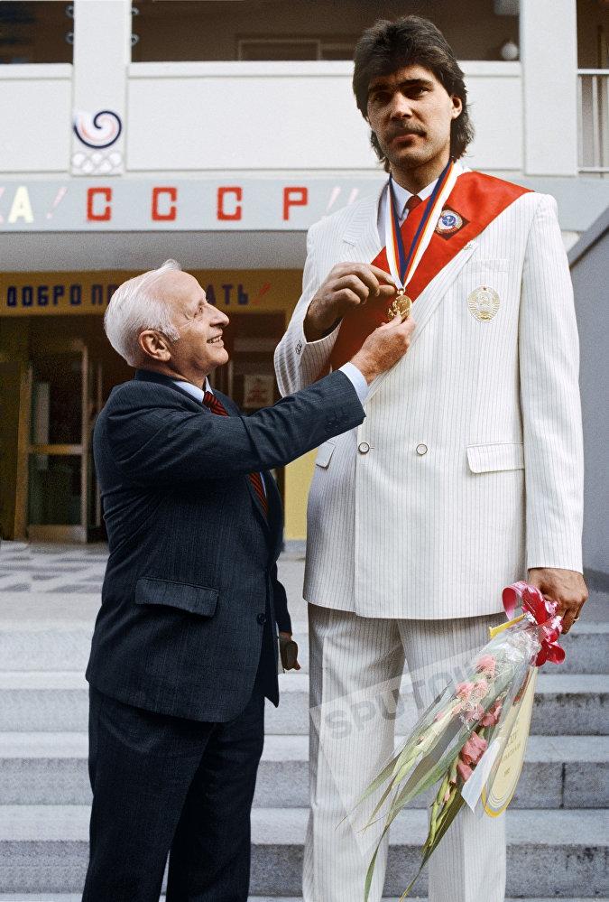 Тренер сборной СССР по баскетболу Александр Гомельский в 1988 году забрал Сабониса в сборную. На фото: Александр Гомельский Арвидас Сабонис с золотой медалью XXIV Олимпийских игр в Сеуле.