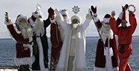 Актеры в костюмах шести Дедов Морозов со всего мира, включая (слева направо) Санта Клауса, Аяз_Ата из Казахстана, из Кыргызстана, российского Деда Мороза, иранского Хаджи Фируз, позируют на фоне озера Иссык-Куль