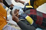 Индийские медицинские работники используют носилки для перевозки раненого пассажира поезда у входа в больницу в Канпуре, после железнодорожной аварии в северном индийском штате Уттар-Прадеш