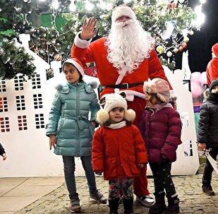 Санта Клаус фотографируется с детьми у новогодней елки в одном из парков грузинской столицы
