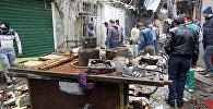 Иракцы смотрят на разрушения после взрывов бомб в оживленном районе Багдада